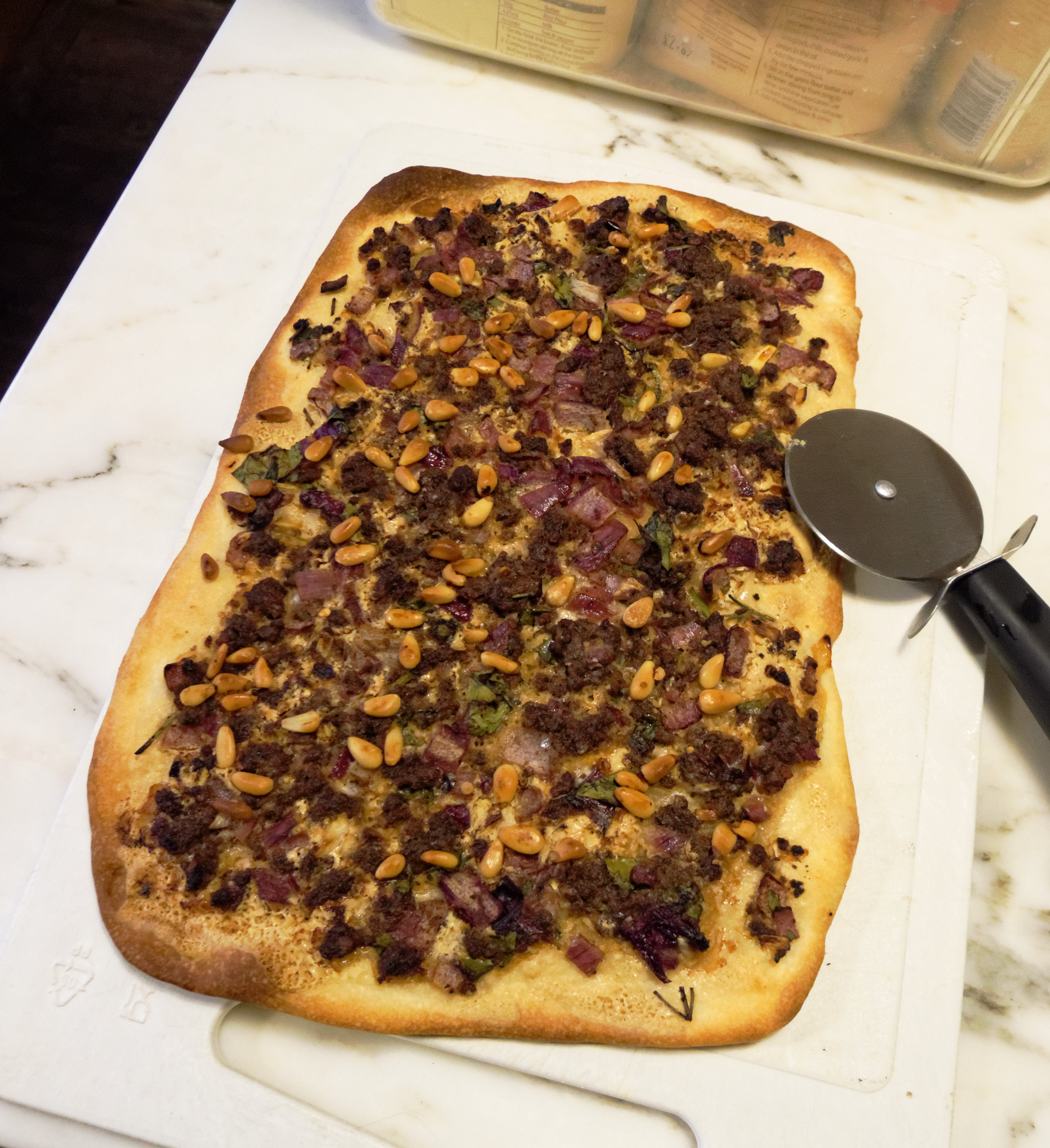 Turkish-style pizza, with minced lamb, spices, pomegranate molasses, parsley and pine nuts
